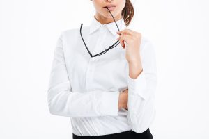 Thoughtful young business woman holding glasses and thinking | 借錢.net