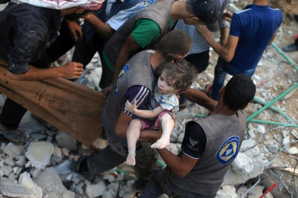 A medic carries an injured girl that survived under debris from what activists said was barrel bombs dropped by forces loyal to Syria's President Bashar Al-Assad in Douma, eastern Ghouta, near Damascus, Syria August 22, 2015. REUTERS/Bassam Khabieh