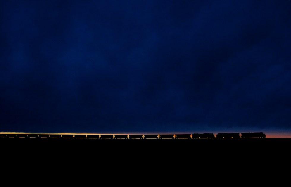 un bello atardecer se oculta atrás del tren de carbón