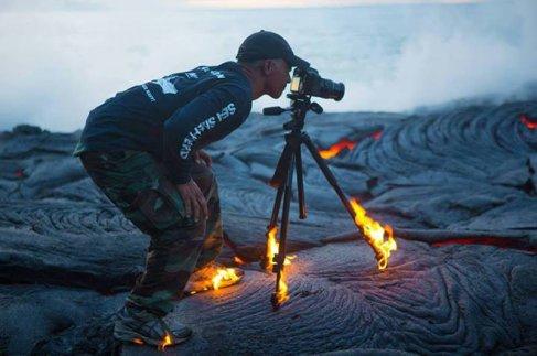 el fotografo kawika singson está parado sobre una delgada costra de lava sólida.