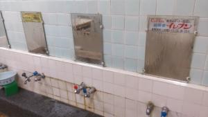 倉敷市レトロ銭湯えびす湯のカランの鏡。懐かしの広告入り