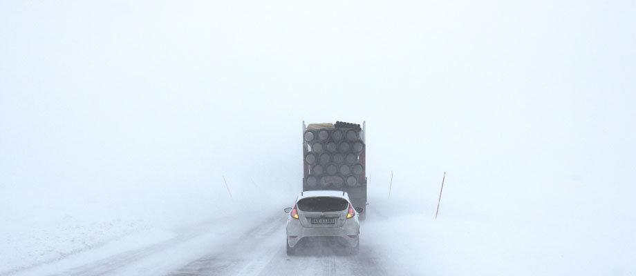 Bil och lastbil ute på vägen i snöstorm