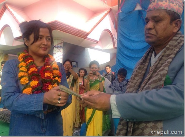 rekha thapa handing over money to school
