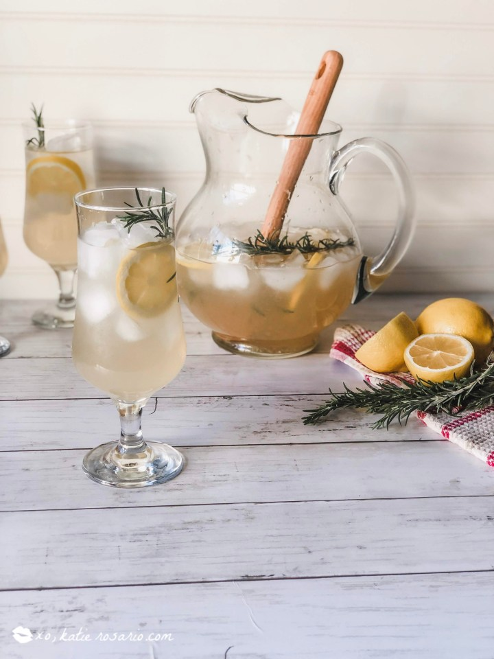 This Rosemary Vanilla Lemonade is an elevated version of your favorite lemonade to keep you cool on a warm day. Make this homemade lemonade recipe on any hot summer day. By using fresh ingredients like rosemary and vanilla, you get a tasty sweet and tart lemonade that's perfect for a large crowd. #xokatierosario #homemadelemonade #lemonaderecipe #lemonadecocktails