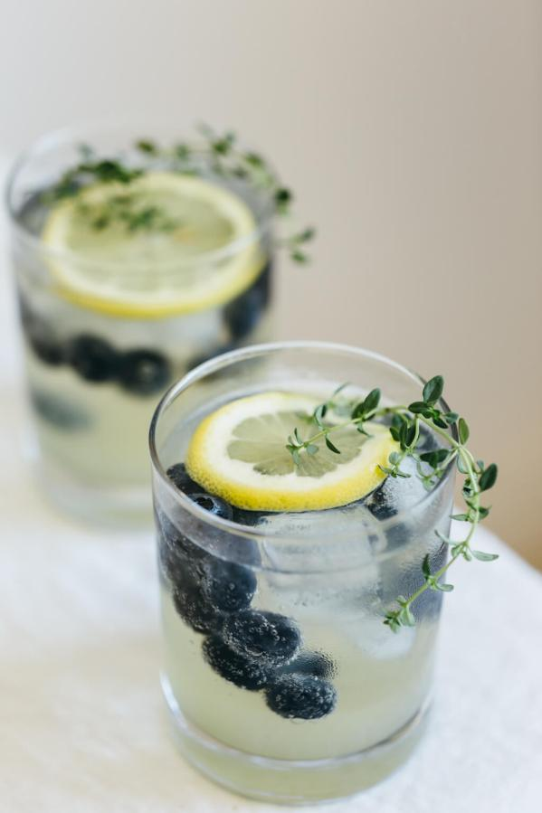 Limoncello Prosecco with Blueberries and Thyme | These sparkling drinks are fantastic for summer entertaining. Whatever sparkling drinks you choose to make this summer, your thirst will be quenched, and you'll stay relaxed and happy in the summer heat. Here are 14 Sparkling Drinks That'll Keep You So Refreshed! #xokatierosario #sparklingdrinks #sparklingcocktails #sparklingnonalcoholicdrinks #summerentertaining