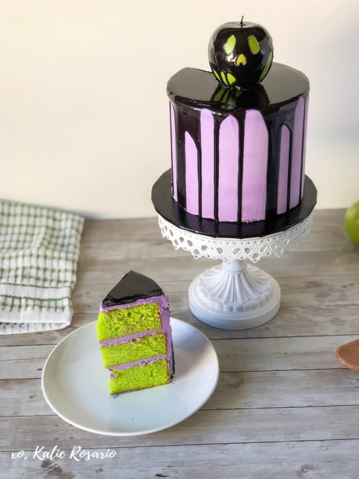 Learn how to make this Spooky Poison Apple Cake for Halloween! Halloween is an excellent time of year to step out of your comfort zone and try new cake decorating tips and tricks! This Poison Apple Cake is made with bright green vanilla cake layers filled with creamy purple vanilla buttercream and black mirror glaze dripping down the cake. This is an impressive cake that anyone can make! #xokatierosario #halloweencakideas #poisonapplecake #cakedecoratingtipsandtricks