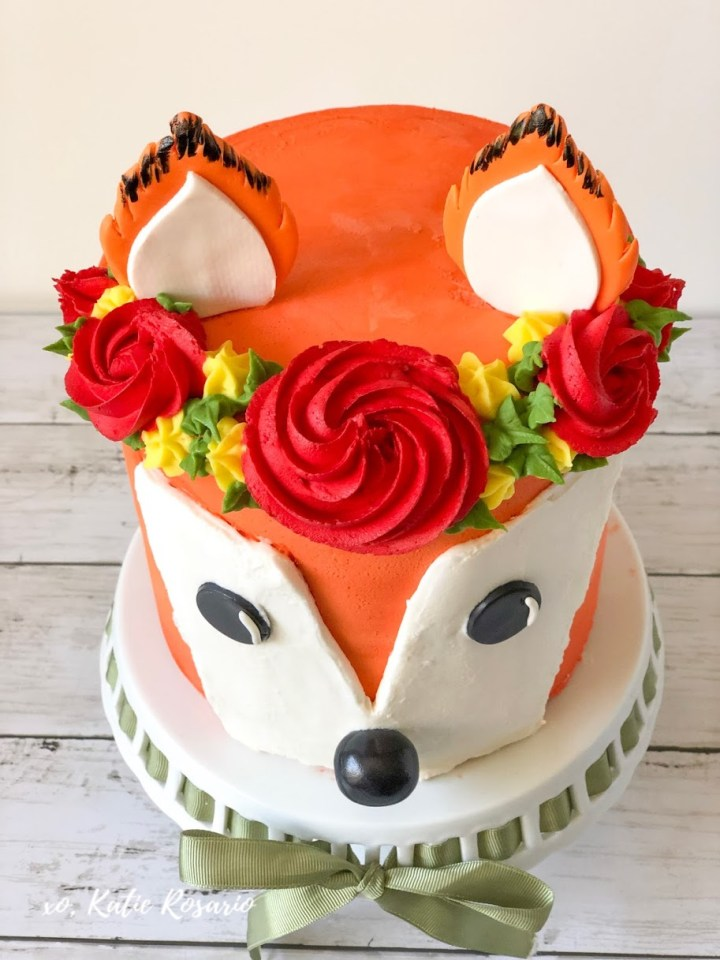 Learn how to make a trendy Woodland Fox Cake with this easy and fun tutorial! I'll show you exactly how to make Woodland Fox cake at home that's perfect for the fall season, baby showers and birthdays! I'll teach you basic cake decorating techniques that will help you become a better cake decorator! You'll also make a colorful buttercream flower crown to complete this woodland fox cake! #xokatierosario #woodlandfoxcake #foxcaketutorial #buttercreamcakeideas #cakedecoratingtipsandtricks