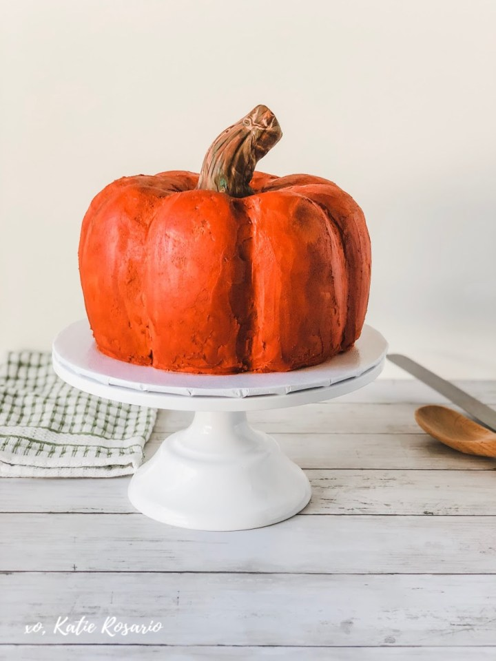 Sweater weather & this pumpkin spice cake is perfect for Fall! This pumpkin spice cake is made with soft pumpkin spice cake layers & creamy vanilla buttercream that's decorated to look like a pumpkin you might find at your local pumpkin patch. This pumpkin spice cake is perfect for all fall celebrations and something that will undoubtedly impress your friends & family. #xokatierosario #pumpkinspicecake #pumpkinbundtcake #fondantpumpkincake