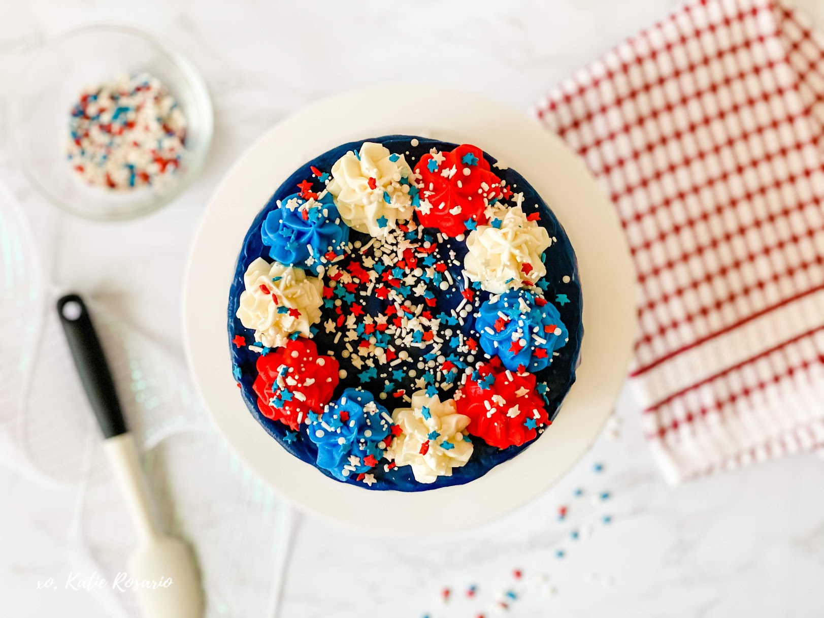 Learn how to make a patriotic cake for the Fourth of July? This Red, White & Blue Drip Cake is perfect for the Fourth of July. It's bright and patriotic while tasting delicious! This Red, White & Blue Drip Cake is made with fluffy vanilla cake layers, filled with patriotic vanilla buttercream and chocolate ganache dripping down the sides of the cake. #xokatierosario #PatrioticCake #dripcake #4thofjulycake #cakedecoratingtips