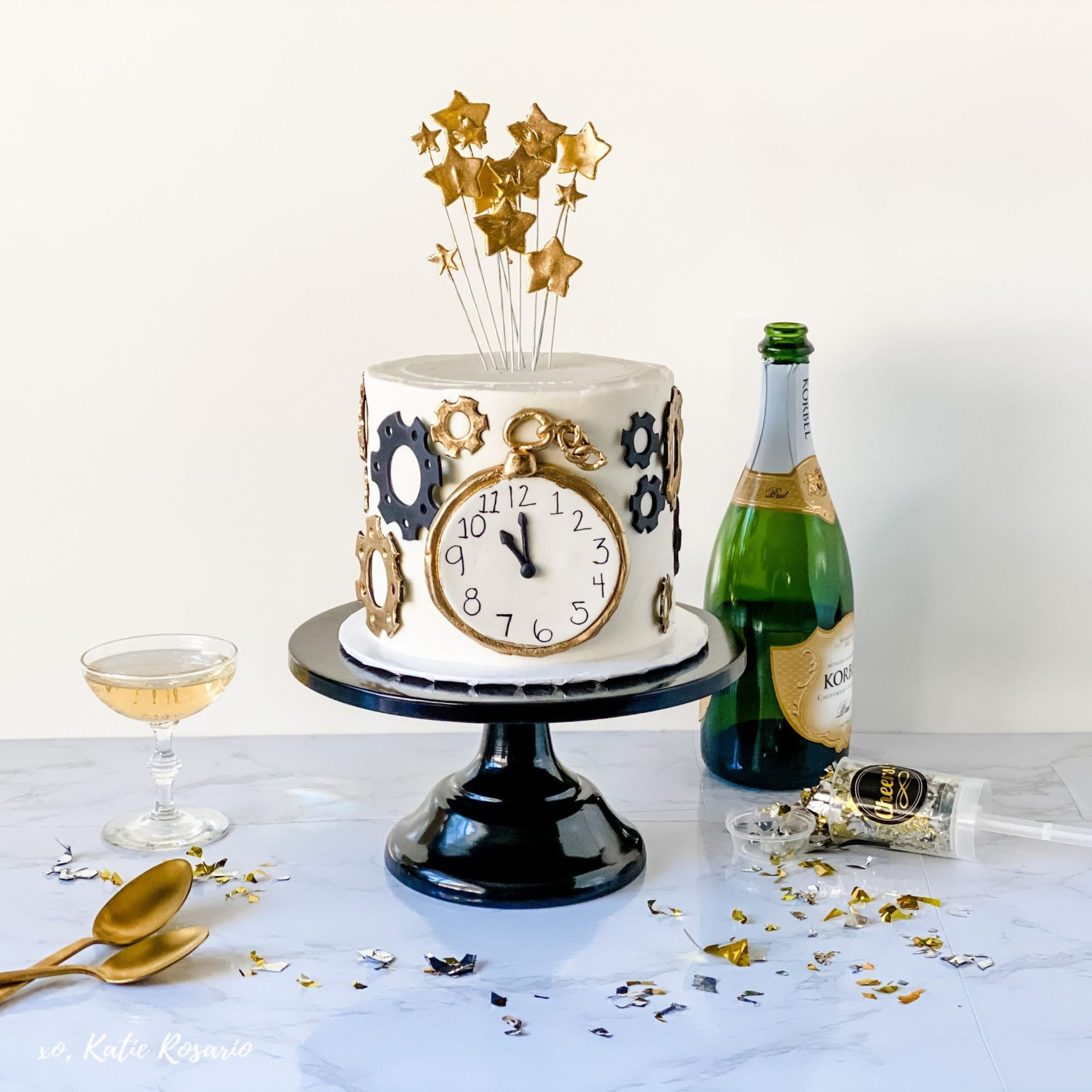Learn how to make this New Year's Eve Champagne Cake that's elegant and delicious. And I am obsessed with these fondant decorations. This makes me excited to teach you because it's excellent practice when you are making a custom cake. Here is the perfect cake to ring in the new year. #xokatierosario #katierosariocake #champagnecake #newyearsevecake #cakedecoratingtips