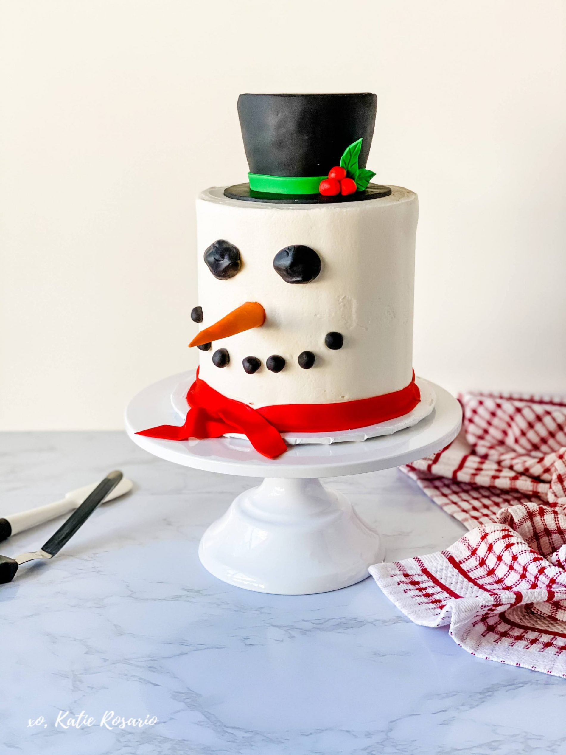 Learn how to make this adorable Snowman Cake for the holidays. This Snowman cake is made of fluffy vanilla cake layers filled with creamy vanilla buttercream and cute fondant decorations. Here you'll learn how to make fondant decorations that'll surely impress your friends and family. #xokatierosario #snowmancake #christmascake #cakedecoratingforbeginners #cakedecoratingtips