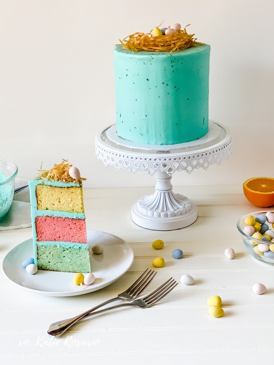 Learn how to make this Speckled Robin Egg Cake that's perfect for a Happy Easter! This Robin Egg Cake is made with soft orange almond cake layers with creamy vanilla buttercream, phyllo birds nest, and Cadbury chocolate eggs. This tutorial is made with a beginner mindset so anyone can make this exciting and delicious Robin Egg Cake!
