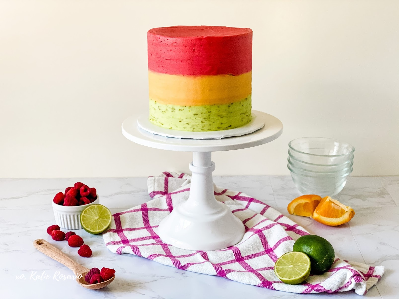 Rainbow Sherbet Cake that tastes just like your favorite summer ice cream. This Rainbow Sherbet Cake is made up of raspberry, orange, and lime cake, and buttercream. Created by Katie Rosario, XOKatieRosario creates beautiful cake decorating techniques that are easy for beginners and strategically designed for any home baker. #xokatierosario.com #cakedecoratingcourse #xokatierosario #katierosariocakes #rainbowsherbet #rainbowcake #rainbowshertbetcake