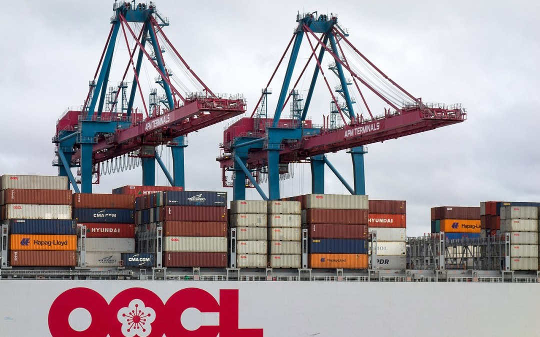 Cranes load containers onto an OOCL container ship.
