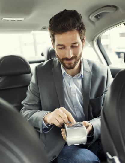 Male customer using credit card to pay for taxi journey
