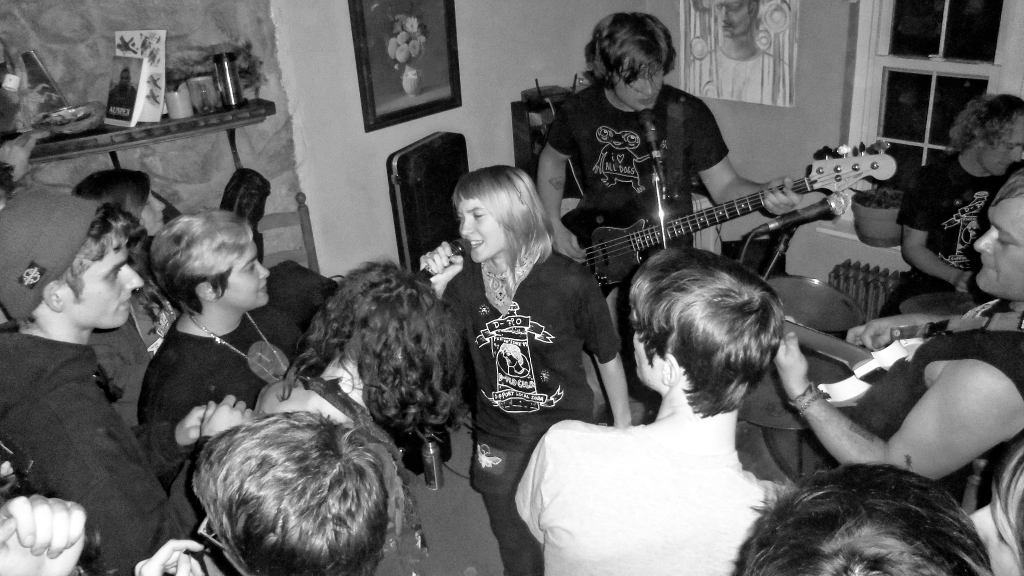 Girl Singing at a house show support youth