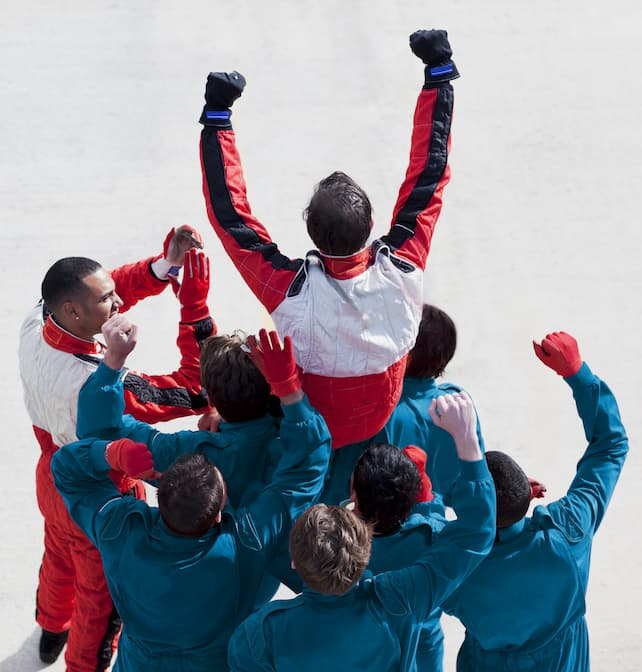 Formula 1 team hold their winning driver up on their shoulders