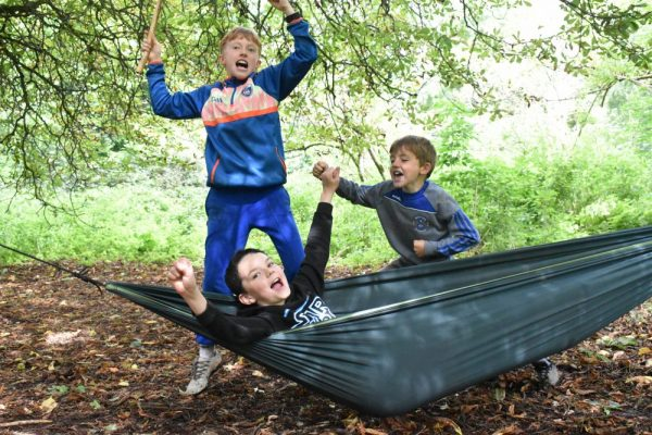 3 boys enjoying playing on the hammocks at Base Camp of their bushcraft birthday party in the forest at Carton House.