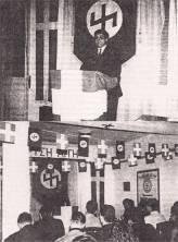"""Πρώτο συνέδριο της ΧΑ, 10/02/1990 στα γραφεία τους. Ο ρούνος Wolfsangel στον τοίχο ήταν, μεταξύ άλλων, και το έμβλημα της 4ης Polizei Division των SS, που ήταν υπεύθυνη για τις σφαγές αμάχων σε Δίστομο και Κλεισούρα, ενώ το ίδιο ακριβώς σήμα είχε και η """"θρυλική"""" (για τους ναζί και τους νεοναζί) 2η Μεραρχία Τεθωρακισμένων των SS """"Das Reich"""" που ευθύνεται για το τρομερό έγκλημα πολέμου, τη σφαγή 642 αμάχων στο χωριό Οραντούρ στη Γαλλία."""