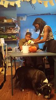 Xzavier Davis-Bilbo and sister Aurie Parris carve a pumpkin in his room