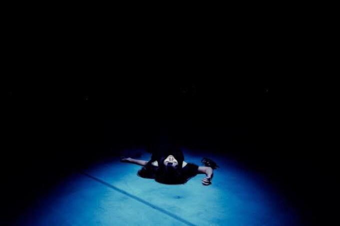 真っ暗な暗闇の中に人が倒れている画像