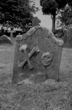 A gravestone with symbols of mortality: bones and skull; as well as a farmer's plough.