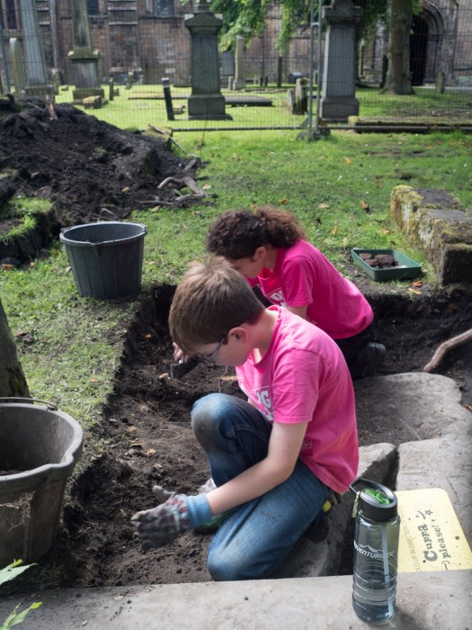 Finlay and Erin extending the trench eastward to reveal the ends of two gravestones