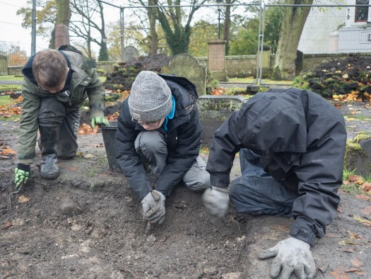 Clearing rubble prior to uncovering another gravestone