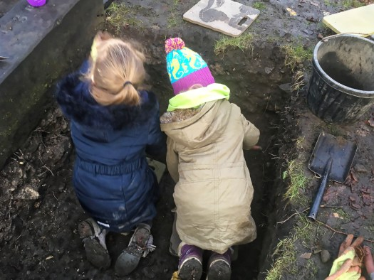 Two young archaeologists practise trowelling in the safety of their test pit.