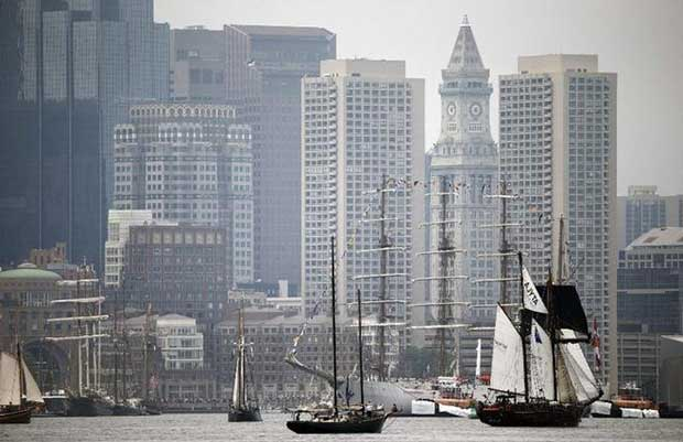 Tall ships pass in front of the skyline during Sail Boston's Parade of Sail on Saturday © Michael Dwyer / AP