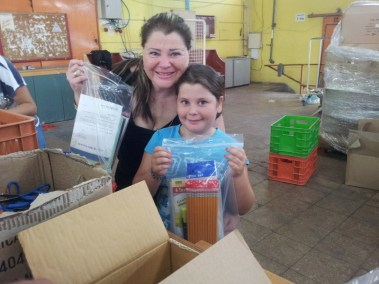Mother and daughter packing stationery kits