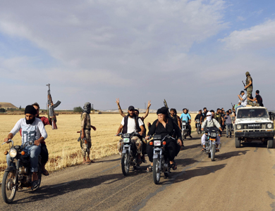 Free Syrian Army fighters gesture and hold their weapon as they ride on their motorcycles in northern Hama countryside