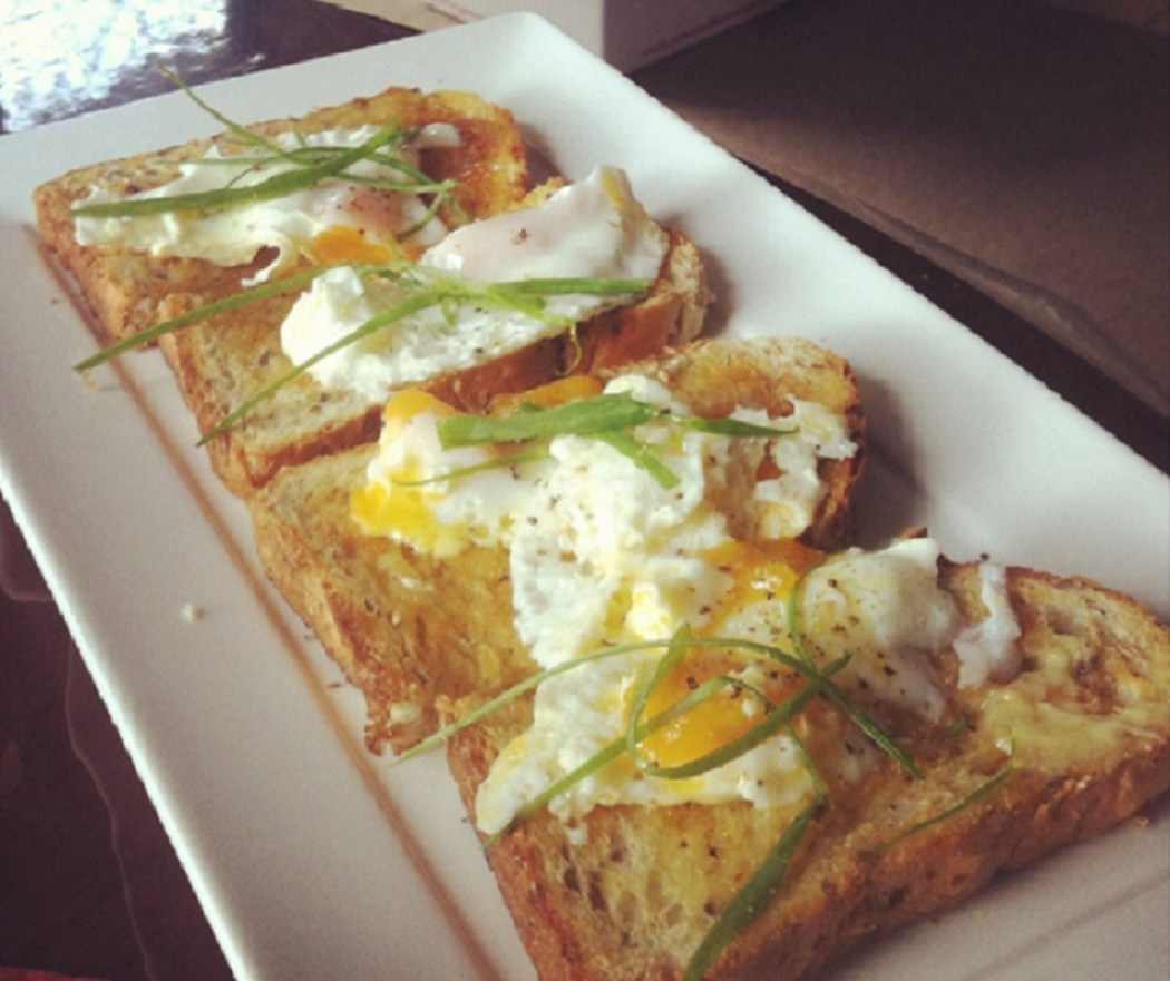 Four poached eggs with garnish on toast