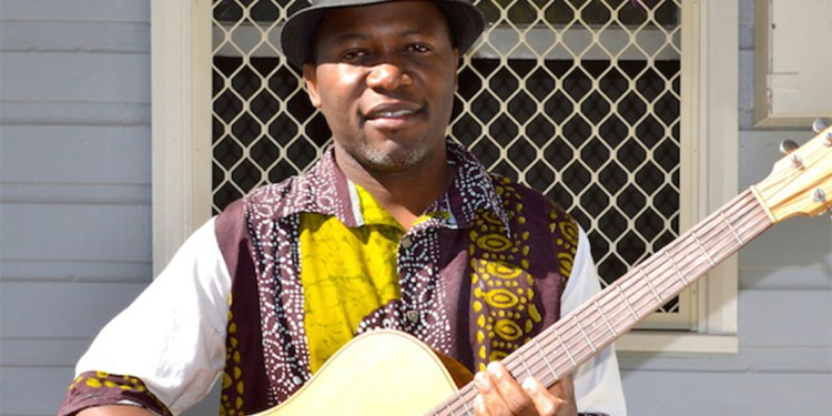 Berias Masseque poses with his guitar