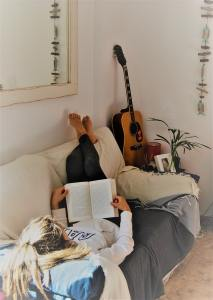 woman-reading-book-while-lying-on-sofa-2257043 (1)