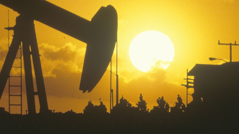 Oil drilling well in the sunset