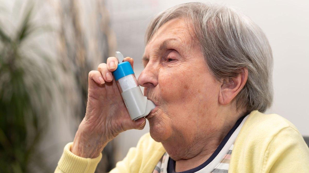 Elderly woman using inhaler