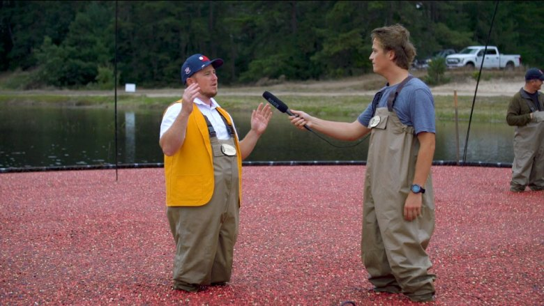 A person is interviewed by another person while standing in a cranberry blog.