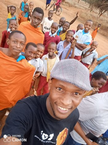 Young Tanzanian man takes a selfie with group of boys in the Massai Wasonjo Community