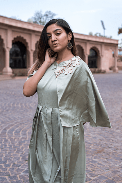 The Pista Green Drape Dress has a mini one sided cape that is embellished with an applique work. The waistline is detailed with pleats and the hemline is draped in a dhoti pattern