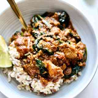 Lamb and spinach curry served over brown rice, and garnished with fresh lime.