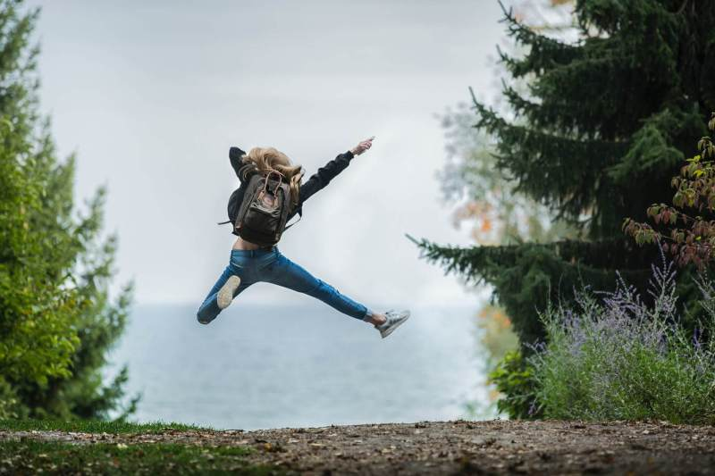 woman jumping wearing green backpack