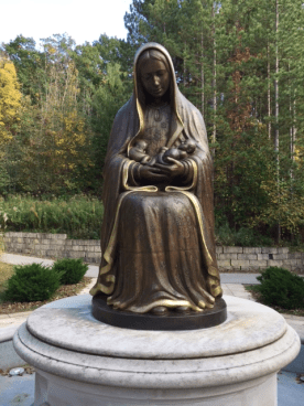 Opposite the church, a statue of Mary holding the aborted