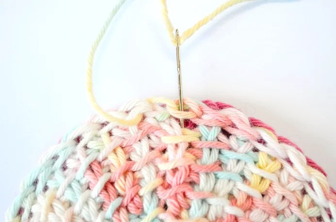 Tunisian crochet face scrubbies - creating an invisible bind off of the last stitch - needle back in the original stitch, going into the fabric