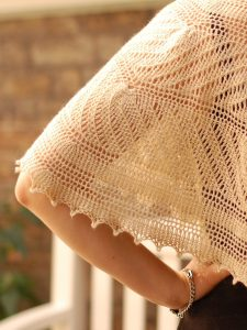 a cream colours lace shawl sits across a woman's back and bent arm.