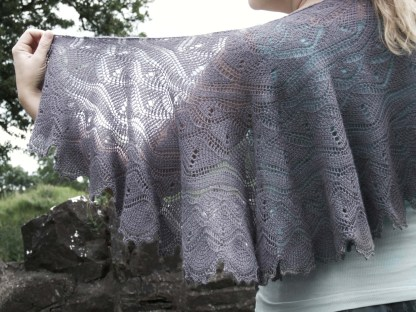 a violet tunisian crochet shawl worn by a woman. She is standing in the countryside, holding part of the shawl up to let light through