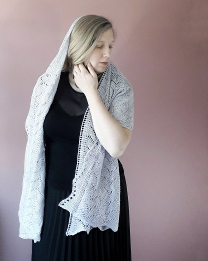 a white woman holds her blonde hair back as a grey lace shawl rests across her shoulders and head. She is dressed in black and stands in front of a light pink wall