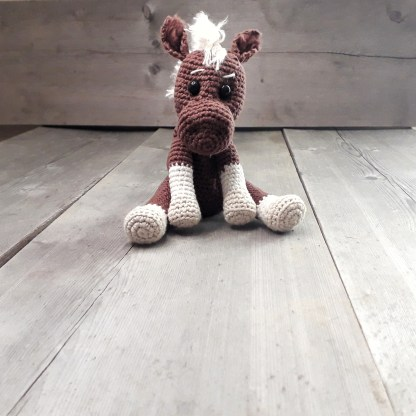 a brown crochet horse soft toy sits with its front hooves resting on a table top