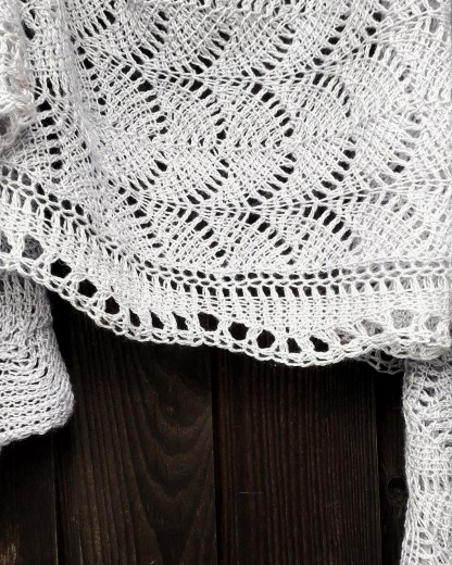 a grey lace shawl hanging on a dark wooden outside wall