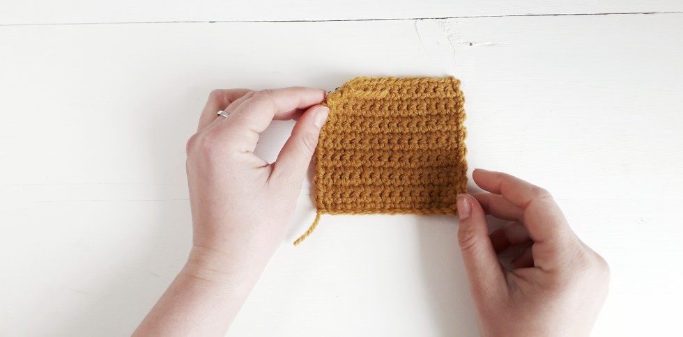 two hands hold a swatch of traditional crochet in yellow yarn against a painted white wooden surface